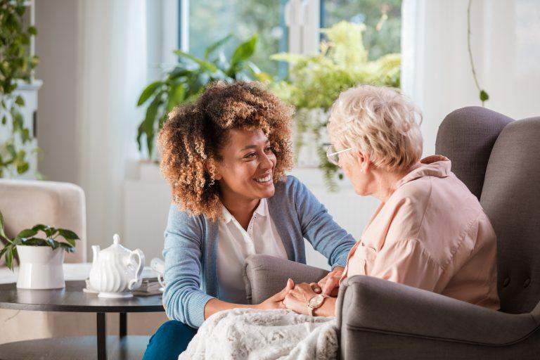 Friendly Nurse Supporting An Eldery Lady